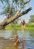 Happy boy and girl play in lake Stock Photography
