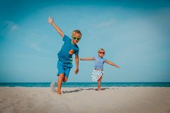 Happy boy and girl run play at beach stock photos