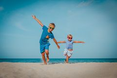 Happy boy and girl run play at beach. Happy boy and girl run play fly at beach, travel to beach concept royalty free stock images