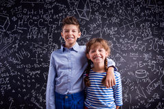 Happy boy and girl at school against big blackboard. Royalty Free Stock Image