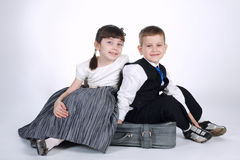 Happy boy and girl sitting on suitcase Royalty Free Stock Photography