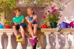 Happy boy and girl sitting on terrace balustrade royalty free stock photography