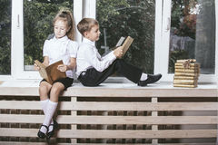 Happy boy and girl sitting on the windowsill reading books on th Royalty Free Stock Photo