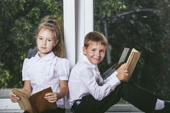 Happy boy and girl sitting on the windowsill reading books on th Stock Image