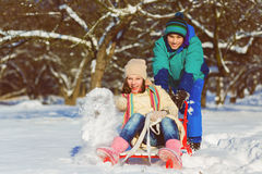 Happy boy and girl sledding in winter outdoor.  Royalty Free Stock Photography