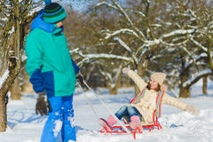 Happy boy and girl sledding in winter outdoor Stock Photos