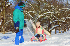 Happy boy and girl sledding in winter outdoor Stock Image