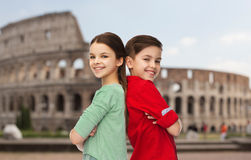 Happy boy and girl standing over coliseum in rome. Childhood, travel, tourism and people concept - happy smiling boy and girl standing back to back over coliseum Royalty Free Stock Photography
