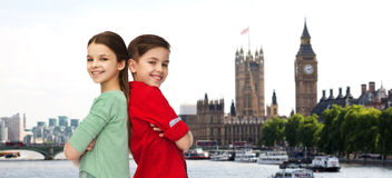 Happy boy and girl standing together over london Stock Photos