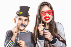 Happy boy and girl, try on funny masks. Two teenagers have fun, and try on funny masks Royalty Free Stock Photos
