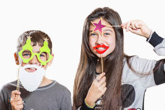 Happy boy and girl, try on funny masks. Two teenagers have fun, and try on funny masks Royalty Free Stock Photo