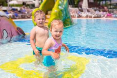 Happy boy and girl twins at the pool. On summer holidays royalty free stock photography