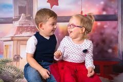 Happy boy and girl twins in christmas scenery. Happy boy and girl twins posing in christmas scenery stock photo