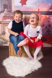 Happy boy and girl twins in christmas scenery. Happy boy and girl twins posing in christmas scenery stock images