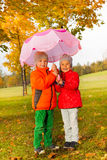 Happy boy and girl with umbrella standing together Royalty Free Stock Images
