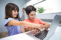 Happy boy and girl using laptop Stock Photo