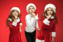 The happy boy and girls in santa claus hats with gift boxes at studio. The surprised and happy boy and girls in santa claus hats with gift boxes at red studio Royalty Free Stock Photography