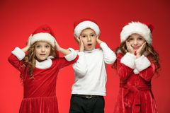 The happy boy and girls in santa claus hats with gift boxes at studio. The surprised and happy boy and girls in santa claus hats with gift boxes at red studio Royalty Free Stock Photo