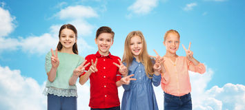 Happy boy and girls showing peace hand sign Stock Images