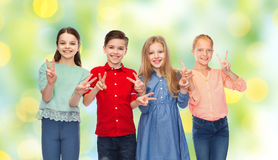 Happy boy and girls showing peace hand sign Royalty Free Stock Image
