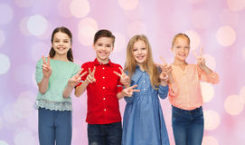 Happy boy and girls showing peace hand sign Royalty Free Stock Images