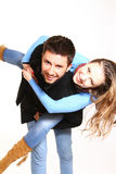 Happy boy giving girl piggyback ride against bright background Royalty Free Stock Photo