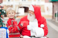 Happy Boy Giving Letter To Santa Claus. Portrait of happy boy giving letter to Santa Claus in courtyard Royalty Free Stock Photography