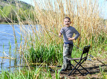 Happy boy giving a thumbs up as he stands fishing Stock Photo