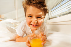 Happy boy with glass of fresh juice in his bedroom Royalty Free Stock Image