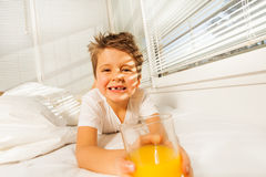 Happy boy with glass of juice in sunny morning Stock Photography