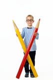 Happy boy in glasses and bowtie posing full length with a huge pencil. Educational concept. Isolated over white. Stock Image