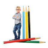 Happy boy in glasses and bowtie posing full length with a huge pencil. Educational concept. Isolated over white. Royalty Free Stock Photo