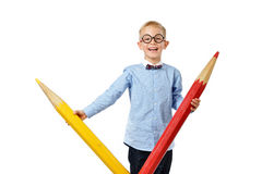 Happy boy in glasses and bowtie posing with a huge pencil. Educational concept. Isolated over white. Royalty Free Stock Photos