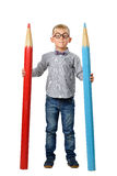 Happy boy in glasses and bowtie posing with a huge pencil. Educational concept. Isolated over white. Royalty Free Stock Images