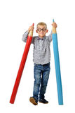 Happy boy in glasses and bowtie posing with a huge pencil. Educational concept. Isolated over white. Stock Photos