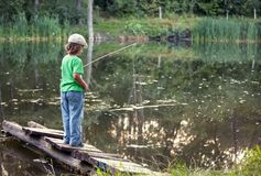 Happy boy go fishing on the river, one children fisherman with a. Happy boy go fishing on the river, one boy fisherman with a fishing rod on the shore of the Royalty Free Stock Image