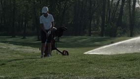Happy boy golfer. Cheerful junior boy on the golf course at sunset stock video footage