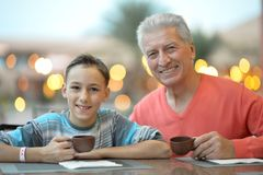 Happy boy with grandfather at breakfast Stock Image