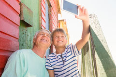 Happy boy with grandfather taking selfie. While sitting by wall Royalty Free Stock Photography