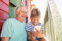 Happy boy with grandfather using smart phone while sitting by wall. At beach Royalty Free Stock Photo