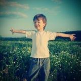 Happy boy on green field Royalty Free Stock Photo