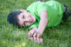 Happy boy in green lying on the green glade Stock Photo