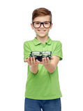 Happy boy in green polo t-shirt holding eyeglasses Royalty Free Stock Image