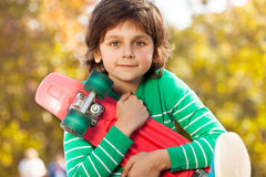 Happy boy in green sweater with red skateboard Royalty Free Stock Images