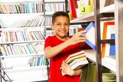 Happy boy with hand on bookshelf holds many books Stock Photos