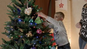 Happy boy hanging gingerbread on christmas tree with mother stock video footage