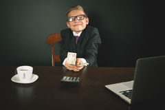 Happy boy has earned a lot of money. Banker holds in hand American dollars. Cunning business boy. Successful school boy. Success concept. Business suit. Stock Stock Images