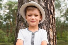 Happy boy in the hat is smiling near the tree trunk. Happy childhood concept. Beautiful smart and smiling kid having fun outdoor. Happy boy in the hat is smiling royalty free stock photos