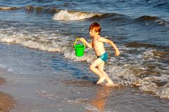 Happy boy having fun on the background of sea playing with buck. And wate in sunset reys. Black sea in ukraine Stock Photos