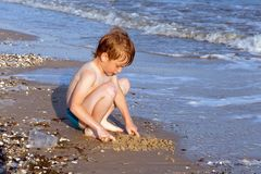 Happy boy having fun on the background of sea playing with sand. And water in sunset reys. Black sea in ukraine Stock Photos